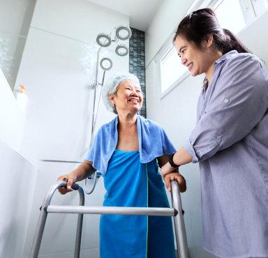 caregiver assisting senior woman in taking a bath