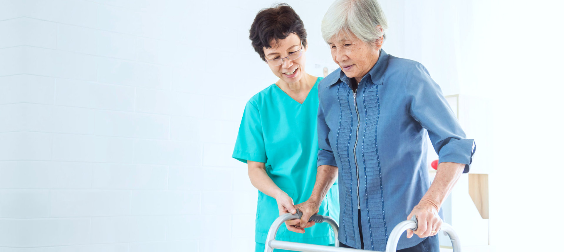 female caregiver assisting senior woman to walk indoor