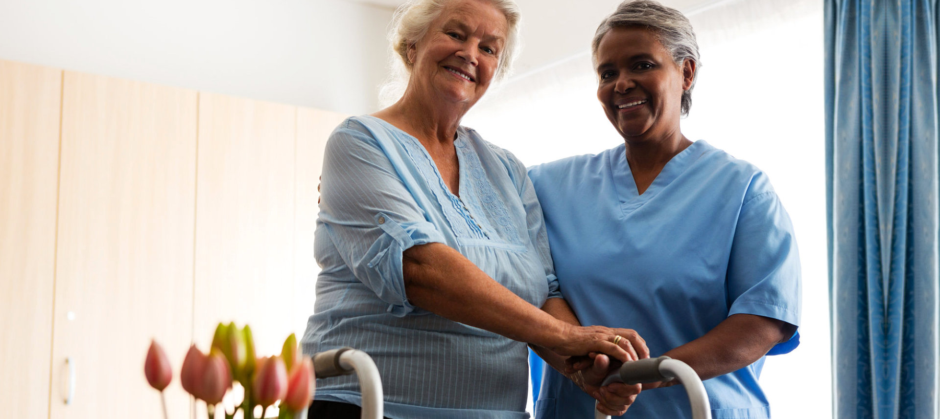 female caregiver hugging senior woman in an adult home