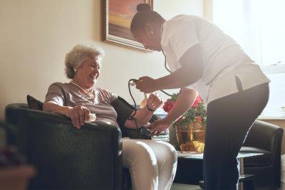 caregiver checking senior womans health