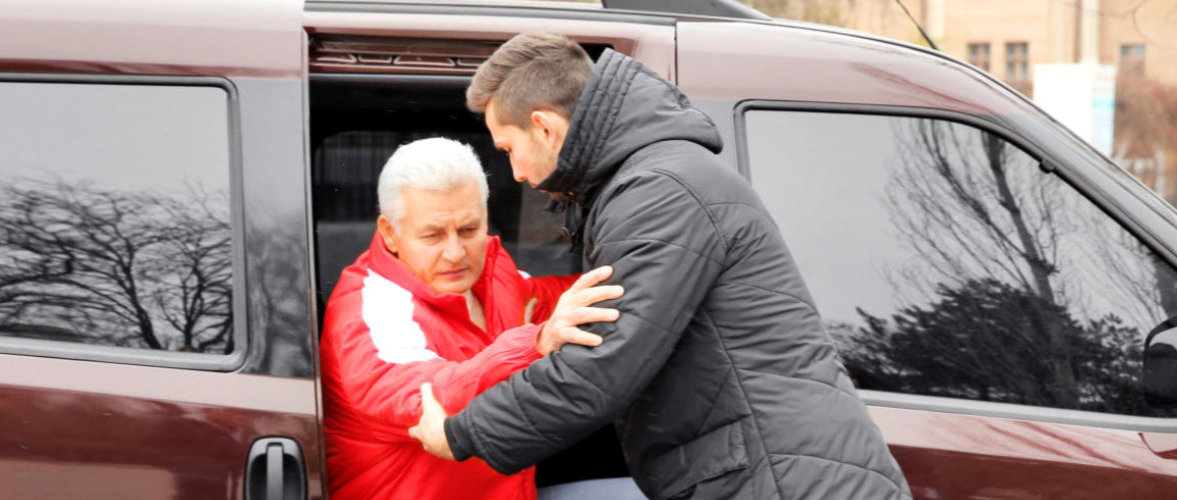 caregiver assisting senior man to sit