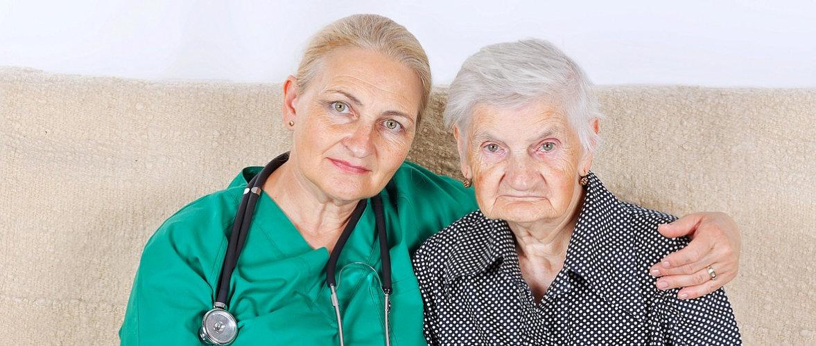female nurse hugging senior woman on a couch