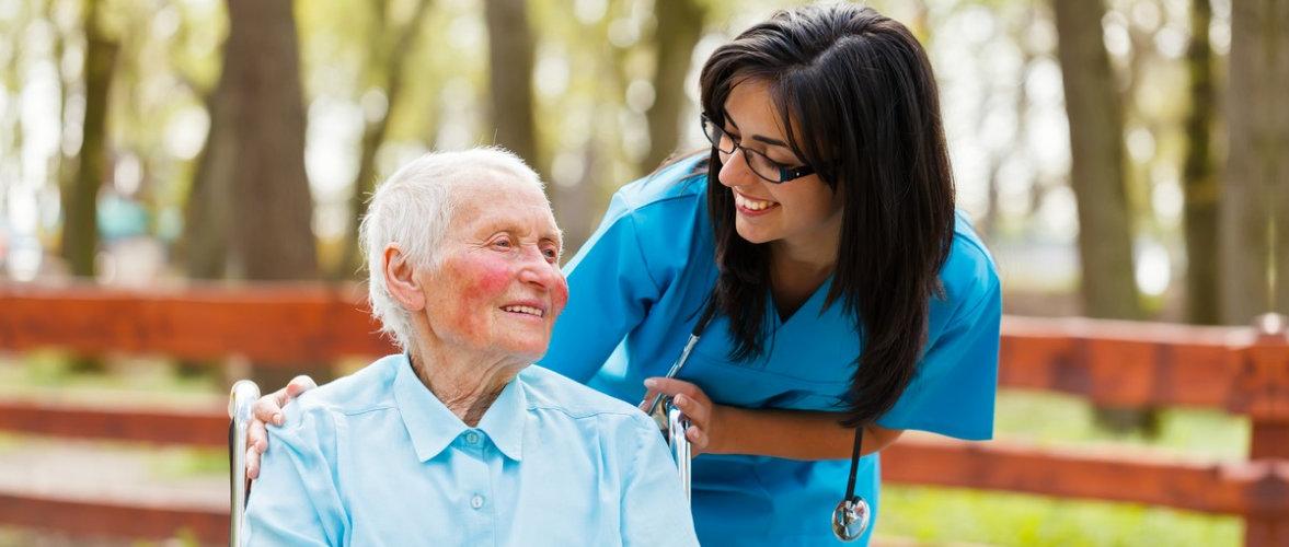 senior man and female caregiver having a walk outdoor